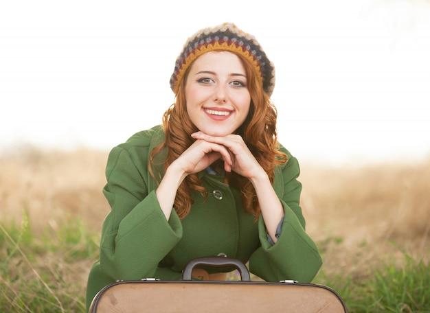 Рыжая девушка с чемоданом сидит на осенней траве
