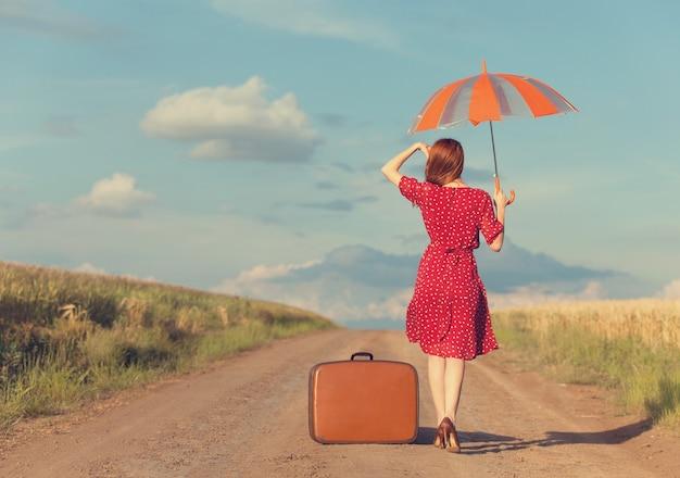 屋外で傘とスーツケースを持つ赤毛の女の子