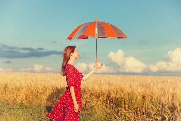Рыжая девушка с зонтиком в поле