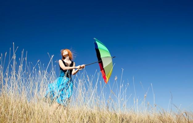 Рыжая девушка с зонтиком на ветреной траве луг.
