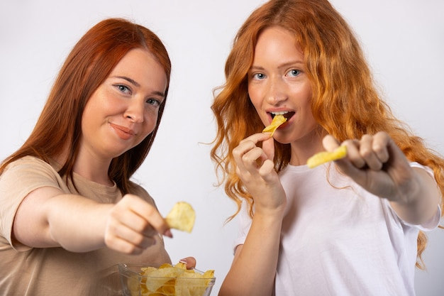 赤毛の女の子はチップを食べて孤立したポーズをとっています