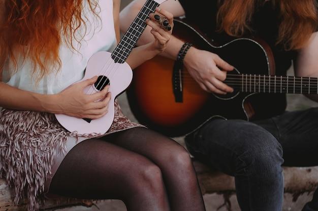 赤毛の男と女がアコースティックギターとウクレレを弾いています。屋外