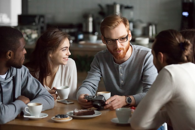 Redhead guy showing camera photos to diverse friends in cafe