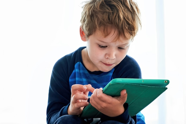 Redhead kid boy playing games on tablet