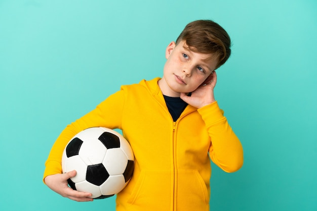 Redhead kid playing football isolated on blue background having doubts