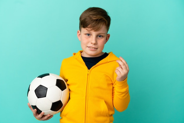 Redhead kid playing football isolated on blue background making money gesture