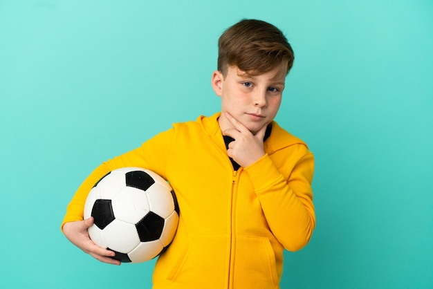 Redhead kid playing football isolated on blue background thinking