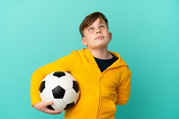 Рыжий ребенок играет в футбол на синем фоне и смотрит вверх