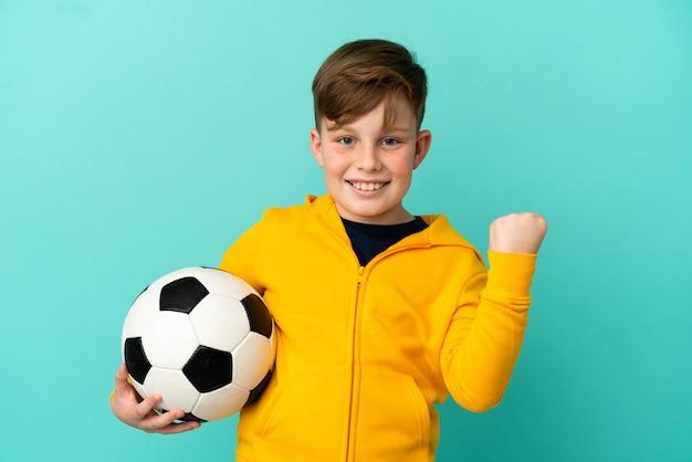 Рыжий ребенок играет в футбол на синем фоне празднует победу в позиции победителя