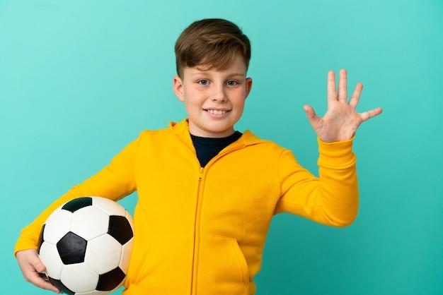 Рыжий ребенок играет в футбол на синем фоне, считая пять пальцами