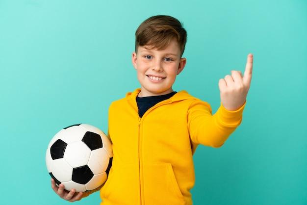 Рыжий ребенок играет в футбол на синем фоне, делая приближающийся жест