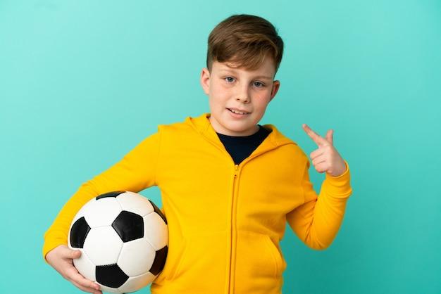 엄지손가락 제스처를 주는 파란색 배경에 고립 축구를 하는 빨간 머리 아이