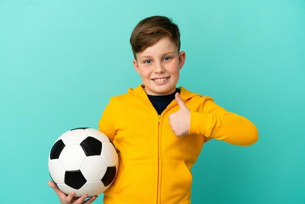 Рыжий ребенок играет в футбол, изолированные на синем фоне, показывает палец вверх