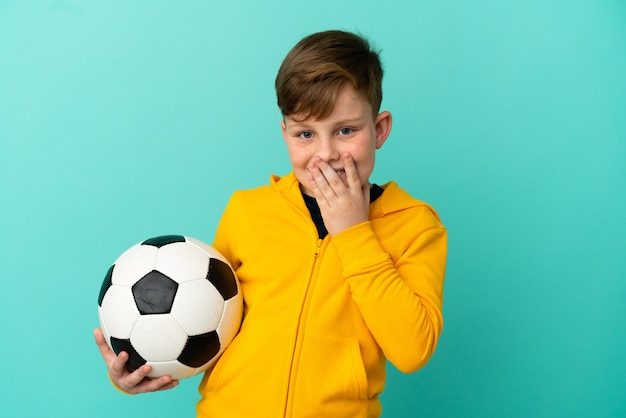 Рыжий ребенок играет в футбол, изолированные на синем фоне, счастливый и улыбается, прикрывая рот рукой