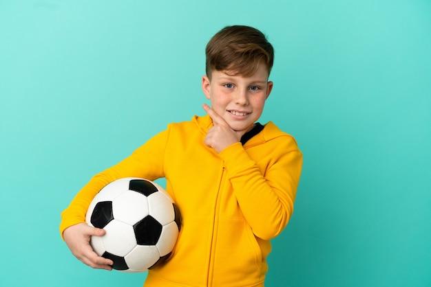 Рыжий ребенок играет в футбол на синем фоне счастливым и улыбается