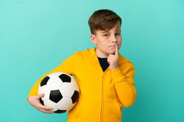 Рыжий ребенок играет в футбол на синем фоне, сомневаясь, глядя вверх