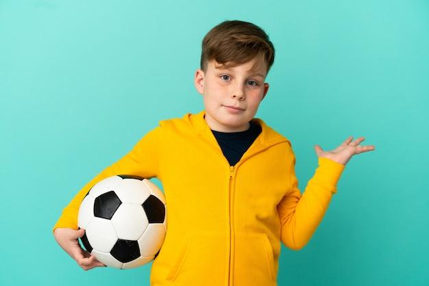 파란 배경에 격리된 축구를 하는 빨간 머리 아이는 손을 드는 동안 의심을 품고 있다