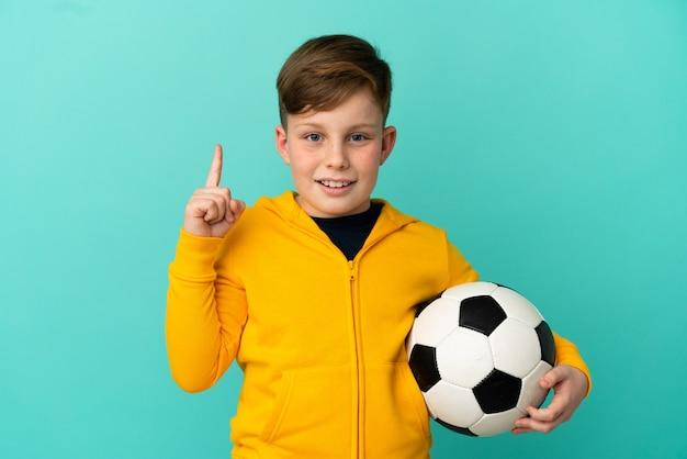 Рыжий ребенок играет в футбол на синем фоне, намереваясь реализовать решение, подняв палец вверх