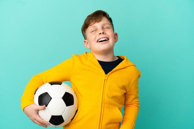 Рыжий ребенок играет в футбол на синем фоне смеется