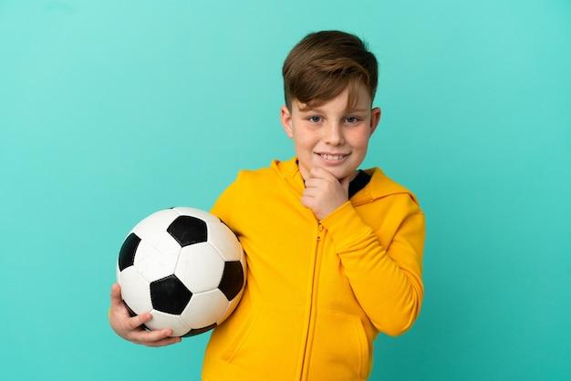 Рыжий ребенок играет в футбол на синем фоне, глядя в сторону и улыбается