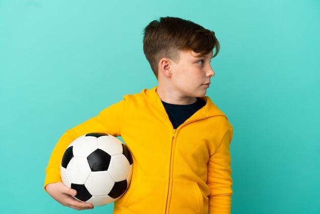 Рыжий ребенок играет в футбол на синем фоне, глядя в сторону
