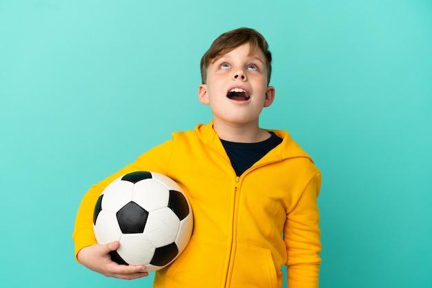 파란 배경에 격리된 축구를 하는 빨간 머리 아이가 올려다보고 놀란 표정으로