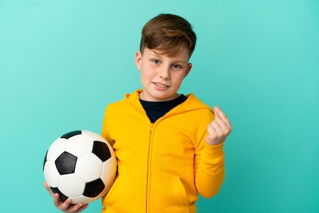 Рыжий ребенок играет в футбол на синем фоне, делая денежный жест