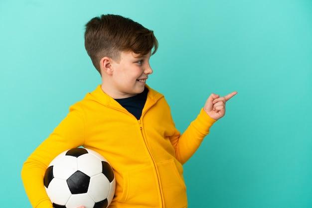 Рыжий ребенок играет в футбол на синем фоне, указывая пальцем в сторону и представляет продукт
