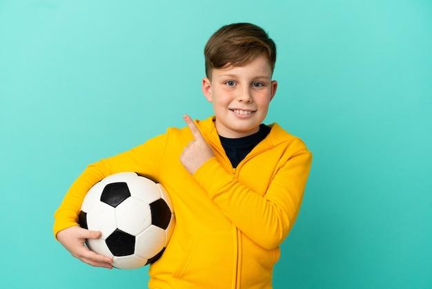 Рыжий ребенок играет в футбол на синем фоне, указывая в сторону, чтобы представить продукт