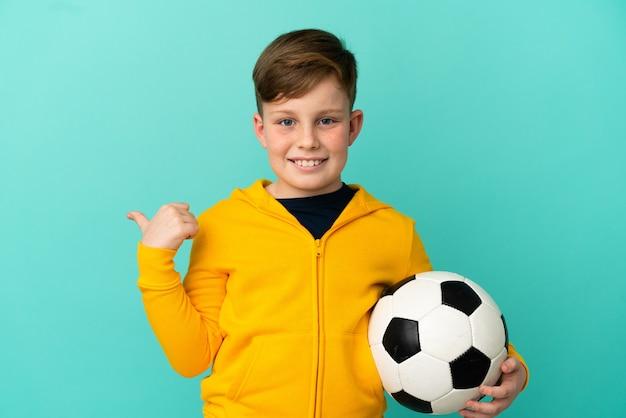 제품을 제시하기 위해 측면을 가리키는 파란색 배경에 고립 된 축구를 하는 빨간 머리 아이
