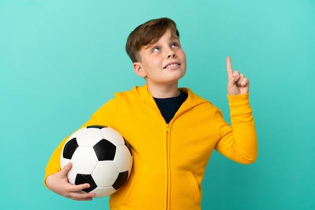 Рыжий ребенок играет в футбол на синем фоне, указывая на отличную идею