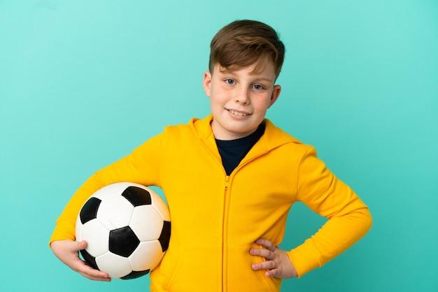 Рыжий ребенок играет в футбол на синем фоне позирует с руками на бедрах и улыбается