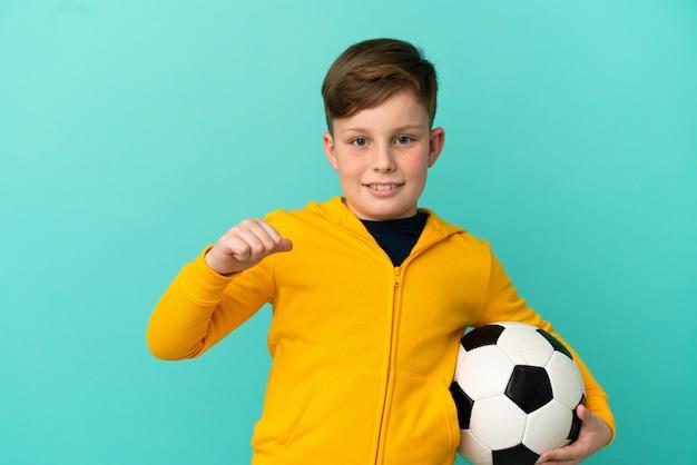 Рыжий ребенок играет в футбол на синем фоне, гордый и самодовольный