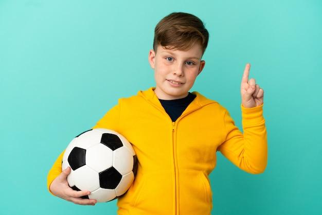 Рыжий ребенок играет в футбол на синем фоне, показывая и поднимая палец в знак лучших