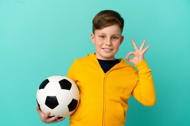 Рыжий ребенок играет в футбол на синем фоне, показывая пальцами знак ок