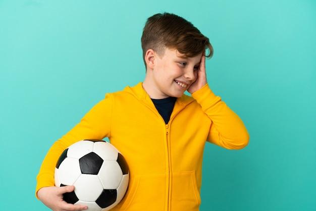 Рыжий ребенок играет в футбол на синем фоне, много улыбаясь