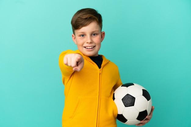 파란 배경에 격리된 축구를 하는 빨간 머리 아이는 놀라고 앞을 가리켰다
