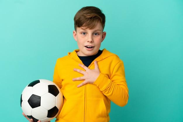 Рыжий ребенок играет в футбол на синем фоне удивлен и шокирован, глядя вправо