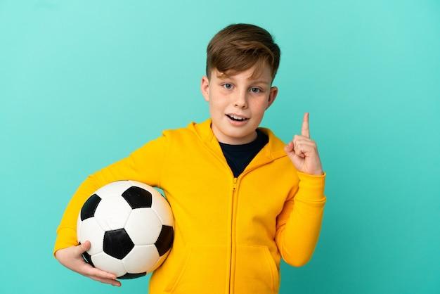 Рыжий ребенок играет в футбол на синем фоне, думая об идее, указывая пальцем вверх