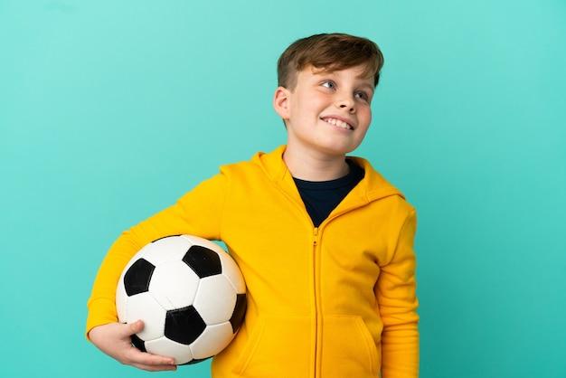 파란 배경에 격리된 축구를 하는 빨간 머리 아이는 올려다보는 동안 아이디어를 생각하고 있다