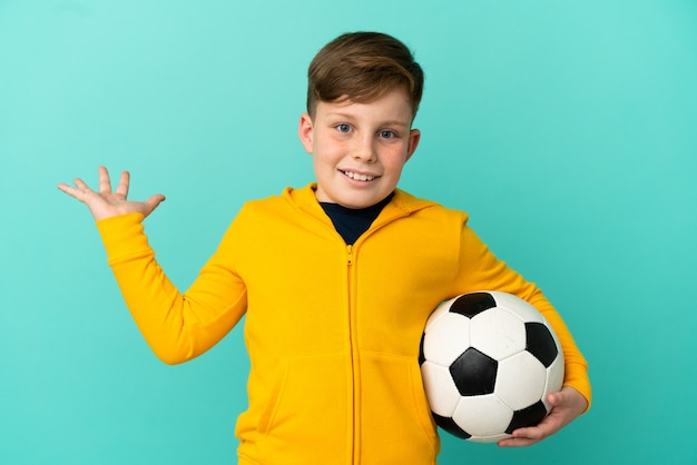 Рыжий ребенок играет в футбол на синем фоне с шокированным выражением лица