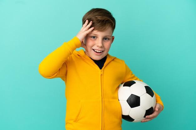 Рыжий ребенок играет в футбол на синем фоне с удивленным выражением лица Premium Фотографии