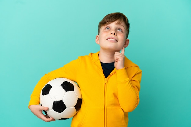 Рыжий ребенок играет в футбол на синей поверхности, думая об идее, глядя вверх