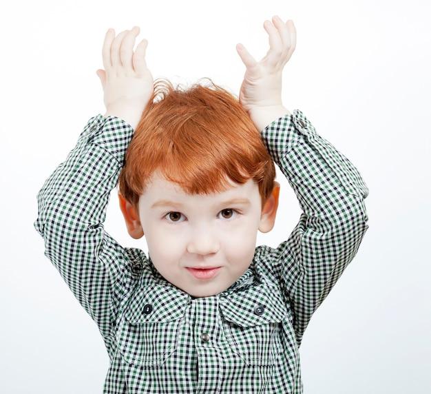 赤毛の少年が両手で遊んで、野獣の角のように頭にかざし、孤立していない、明るい表面にクローズアップ
