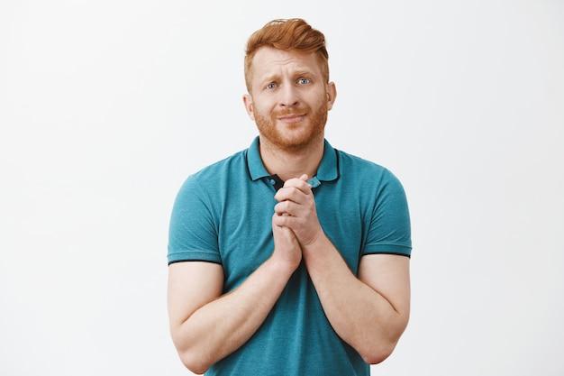 Il maschio dai capelli rossi ha davvero bisogno di aiuto o consiglio, tenendo le mani serrate come in preghiera, alzando le sopracciglia speranzosamente e guardando con un'espressione di supplica carina, chiedendo favore, trovandosi in una situazione problematica
