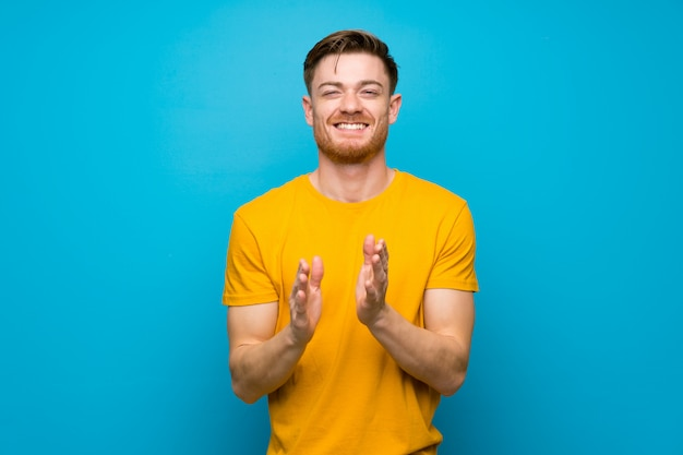Redhead man over blue wall applauding after presentation in a conference