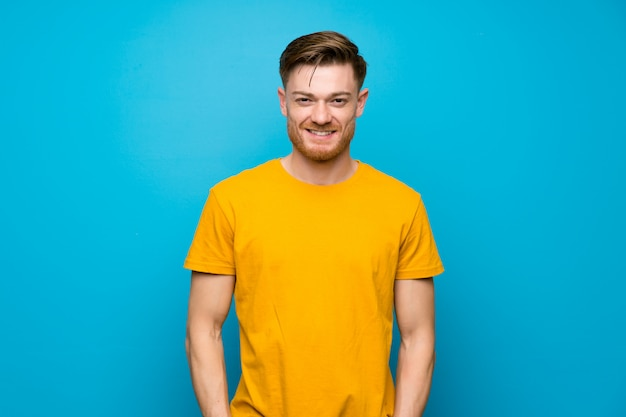 Redhead man over blue wall laughing