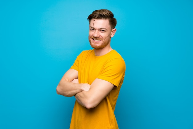 Redhead man over blue wall with arms crossed and looking forward