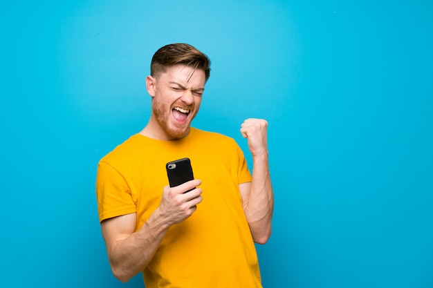 Redhead man over blue wall with phone in victory position