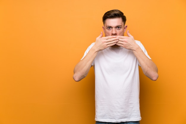 Redhead man over brown wall covering mouth with hands